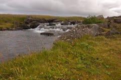 Isländisches Feld mit Strom und dunklen Wolken stockfotografie