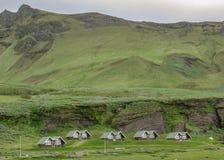 Isländsk bygd med små mycket små hus och berg på bakgrunden i södra Island, Europa royaltyfria bilder