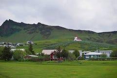 Isländsk stad Vik med dess berömda kyrka på kullen och en liten stad som ett symbol av stillsamma städer i Island Royaltyfri Fotografi