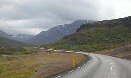 Isländsk väg med moln royaltyfri foto