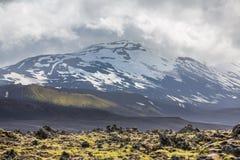 Isländsk vulkan med snö och molnig himmel Arkivbild
