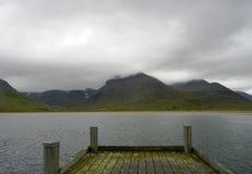 Isländska berg i moln från en pir fotografering för bildbyråer