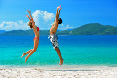 在海滩的一对年轻夫妇在isla的背景假期 免版税库存照片