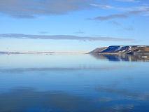 Isla, cielo y mar árticos fotografía de archivo