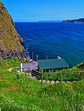 Isla costera del irlandés minúsculo de Carrick-a-Rede con las escaleras que llevan abajo al Atlántico Imágenes de archivo libres de regalías