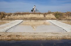 Mature woman biking beside Isla Cristina saltworks, Spain Stock Photography