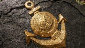ISLA DE ANUMBUS, INDONESIA - 2 DE ABRIL DE 2014: Emblema de oro de la marina de guerra de Indonesia que hace a mano en la roca el Fotografía de archivo