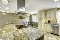 Isla de cocina hermosa con el top del granito, la estufa incorporada y ho Imagenes de archivo