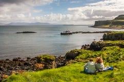 Isla de Lunga, Escocia 8 de septiembre de 2011: Hombre y mujer, sentándose en la hierba que pasa por alto la bahía en reserva de  Foto de archivo libre de regalías