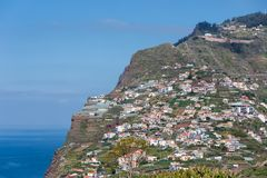 Isla de Madeira con las casas construidas en un acantilado Foto de archivo libre de regalías