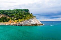 Isla de Palmaria con los árboles verdes, los acantilados, las rocas y agua azul de la turquesa del mar ligur con el fondo dramáti foto de archivo