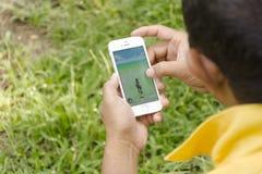 Isla de Samui, Tailandia - agosto 8,2016 Apple sirve con iPhone5s sostenido en una mano que muestra que va su pantalla con Pokemo foto de archivo