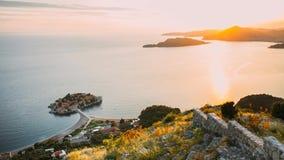 Isla del cierre de Sveti Stefan para arriba en la puesta del sol Montenegro, el Adria almacen de video