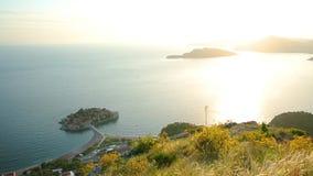 Isla del cierre de Sveti Stefan para arriba en la puesta del sol Montenegro, el Adria metrajes