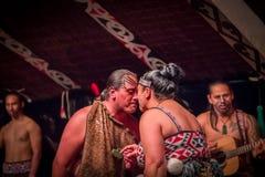 ISLA DEL NORTE, NUEVO SELANDIA 17 DE MAYO DE 2017: Baile de los pares de Tamaki Maori con la cara tradicionalmente tatooed en tra Foto de archivo libre de regalías