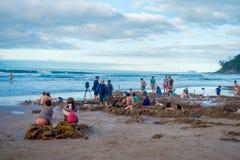 ISLA DEL NORTE, NUEVO SELANDIA 16 DE MAYO DE 2017: Los turistas que cavan sus propias aguas termales en agua caliente varan, Coro Fotografía de archivo
