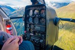 ISLA DEL SUR, NUEVA ZELANDA - 21 DE MAYO DE 2017: Piloto que usa la cabina del comando del helicóptero, en las montañas meridiona Fotografía de archivo