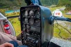 ISLA DEL SUR, NUEVA ZELANDA - 21 DE MAYO DE 2017: Piloto que usa la cabina del comando del helicóptero, en las montañas meridiona Imagen de archivo