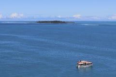 Isla desierta y un barco, South Pacific Foto de archivo libre de regalías