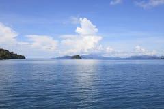 Isla en escena hermosa del mar contra el uso soleado y nublado a del día Fotos de archivo libres de regalías