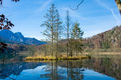 Isla en un lago de la montaña en otoño Foto de archivo