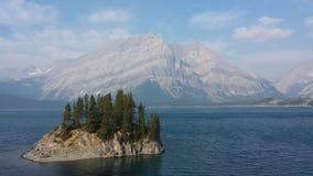 Isla en un lago delante de una montaña Imagenes de archivo