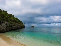 Isla Honduras de Roatan Paisaje de un agua azul tropical del océano del claro de la turquesa y de una playa arenosa Cielo nublado Foto de archivo libre de regalías