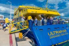 ISLA MUJERES, MEXICO, 10 JANUARI, 2018: Niet geïdentificeerde mensen die een reusachtige blauw en gele boot van kleur inschepen o Royalty-vrije Stock Fotografie