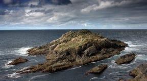 Isla rocosa cerca de la costa de Escocia Fotos de archivo