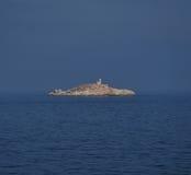 Isla rocosa con el faro cerca de Elba Foto de archivo libre de regalías