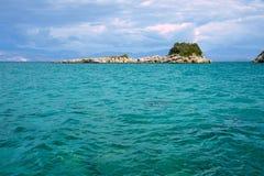 Isla rocosa en el mar jónico y las montañas Fotos de archivo