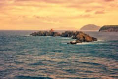 Isla rocosa Greben con el faro en el mar adriático, paisaje marino de la puesta del sol, Dubrovnik, Croacia imagenes de archivo