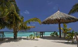 Isla tropical con las palmeras y la playa vibrante asombrosa en Maldivas Parasol blanco en el atolón romántico tropical de Maldiv Fotografía de archivo libre de regalías