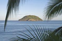 Isla tropical enmarcada por las hojas de palma foto de archivo