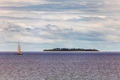 Isla tropical y un barco al lado de él fotografía de archivo