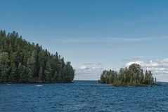 Isla verde en el lago azul en día soleado Foto de archivo libre de regalías