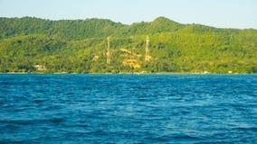 Isla verde grande con la torre del Islam de la mezquita en área remota de la distancia en jawa del karimun fotos de archivo