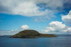Isla y cielo noruegos por completo de clounds Fotos de archivo libres de regalías