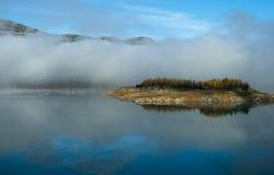 Isla y niebla de la simetría reflejadas en agua imagen de archivo libre de regalías