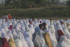 ISLAM FASTEST GROWING RELIGION. Children are playing between rows of praying Muslim women, at Klaten, Java, Indonesia. A new survey by the US based-Pew Research royalty free stock photography