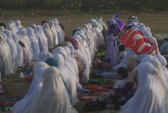 ISLAM FASTEST GROWING RELIGION. Children are playing between rows of praying Muslim women, at Klaten, Java, Indonesia. A new survey by the US based-Pew Research stock photo