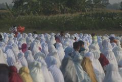 ISLAM FASTEST GROWING RELIGION. Children are playing between rows of praying Muslim women, at Klaten, Java, Indonesia. A new survey by the US based-Pew Research royalty free stock photo