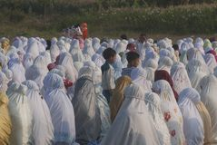 ISLAM FASTEST GROWING RELIGION. Children are playing between rows of praying Muslim women, at Klaten, Java, Indonesia. A new survey by the US based-Pew Research stock photography
