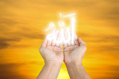 Islam. Hands of man praying to allah god of Islam on blue sky.The words spell is Allah means the God of Islam stock image