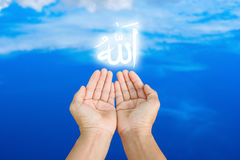 Islam. Hands of man praying to allah god of Islam on blue sky.The words spell is Allah means the God of Islam stock images