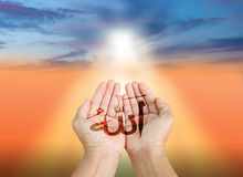 Islam. Hands of man praying to allah god of Islam on a sunset.The words spell is Allah means the God of Islam royalty free stock photo