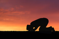 Islam. Man praying to allah god of Islam on sunset royalty free stock image