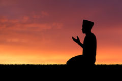 Islam. Man praying to allah god of Islam on sunset royalty free stock images