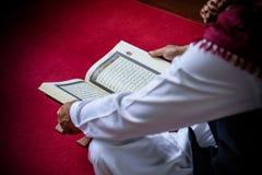 Islam muslim man in muslim dress reading holy book of Koran on s Stock Photography