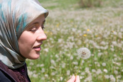 Islam woman and dandelion blowball Royalty Free Stock Photos